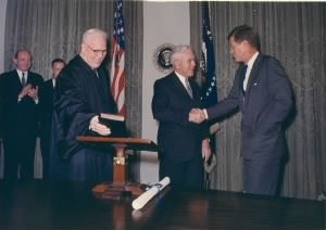 JFK shaking hands with incoming CIA Director John McCone and Chief Justice Earl Warren.jpg